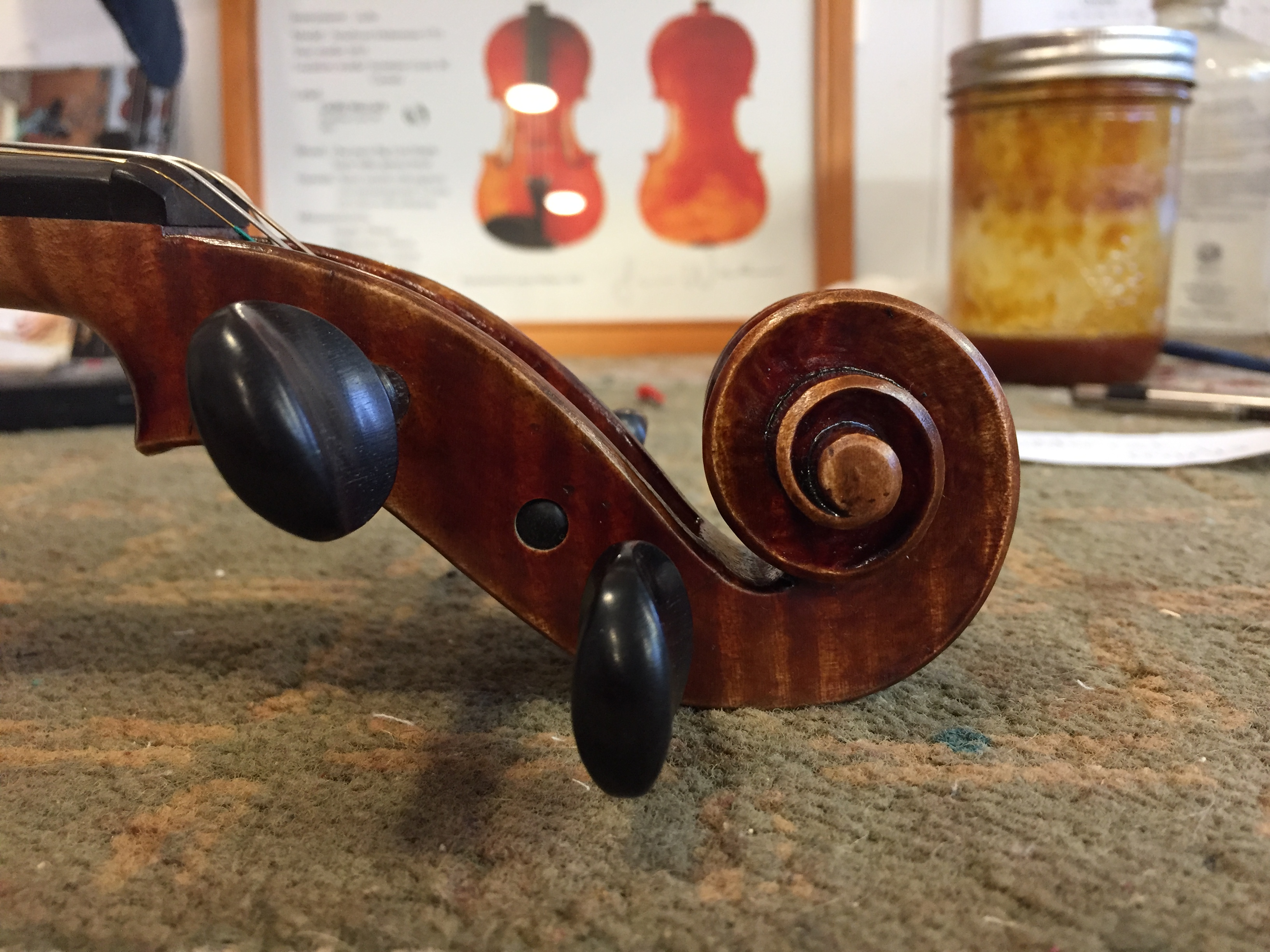 Laura Wallace violin scroll with certificate in background.